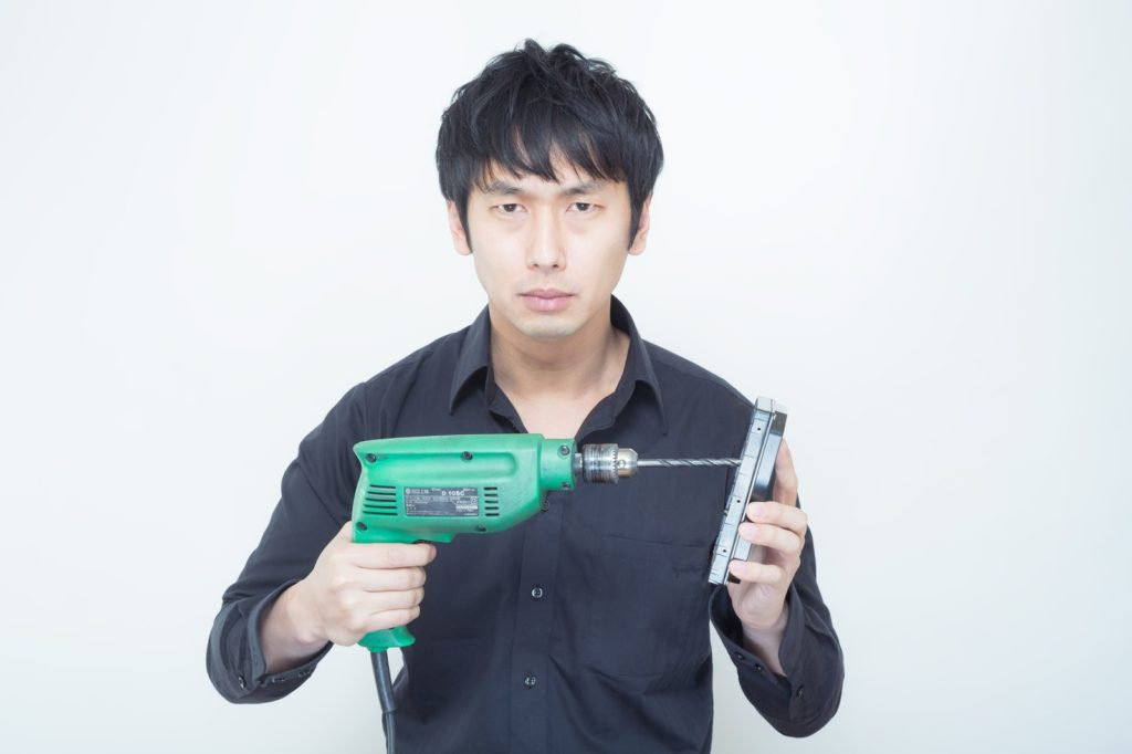 工業用電気ドリルを使ってHDDに穴を空けようとする男性