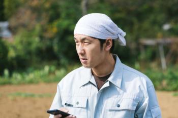 「電波が入らねぇ…」と憤慨する元エンジニアの農民 [モデル:大川竜弥]